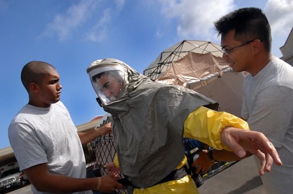 ANDERSEN AIR FORCE BASE, Guam - Senior Amn. Gregory Johnson and Staff Sgt. Al Patague assist Amn. Aaron Guiliano, get into his personal protective equipment to use in the new in-place patient decontamination capabilities  during an exercise April 16th at Andersen Air Force Base, Guam. The IPPDC allows medics to decontaminate patients in the field during a chemical or biological attack. All are members of The Andersen Decontamination Team, 36th Medical Group, Andersen AFB, Guam. (U.S. Air Force photo by Staff Sgt. Vanessa Valentine)