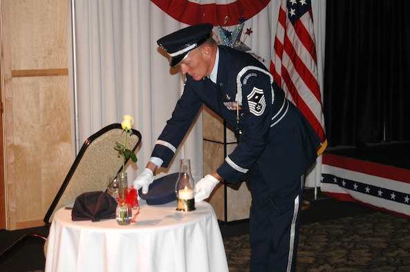 Senior Master Sgt. Joe Shern places a hat on the POW/MIA table at the 169th Intelligence Squadron's dining out in 2005.  The table symbolizes the unit's commitment to never forget those who were taken prisoner, or who have never returned from armed conflict.  Sgt. Shern is a member of the Utah Air National Guard's Base Honor Guard.