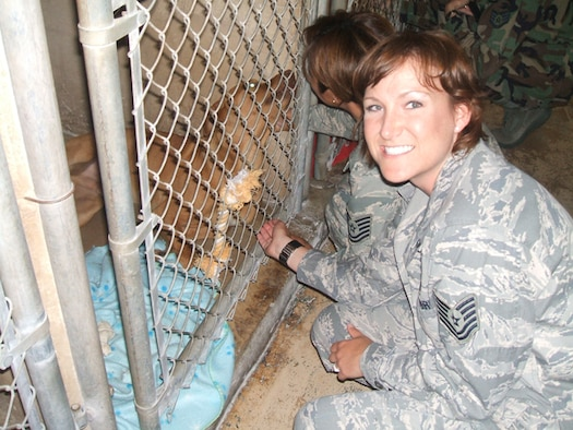 Tech. Sgt. Sandra Deason (facing camera) and Tech. Sgt. Sara Montes visit with one of the animals at the Universal City Animal Shelter after delivering supplies donated by members of the Air Force Personnel Center. (U.S. Air Force photo/File)