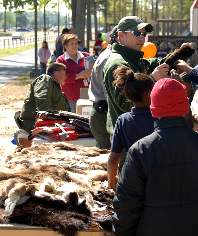 Shelby Staten, U.S. Corps of Engineers, shows a group of children different pelts of fur from local animals. (U.S. Air Force photo by Airman Josh Harbin)