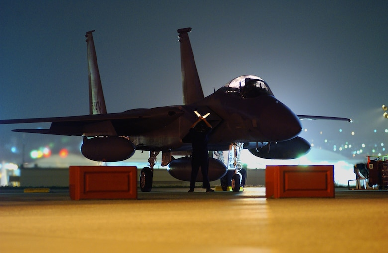 A Kadena Air Base crew chief prepares to marshal out an F-15C Eagle during the early morning hours at Kadena Air Base, Japan, April 23 before its departure to the U.S., symbolizing the end of the Iron Flow program here. The aircraft was one of three jets that left to be transferred to Air National Guard units under Iron Flow which exchanged Kadena's older F-15's with newer models from other active- duty bases. All newer jets have been received and these were the last three older aircraft to be turned in. (U.S. Air Force photo/Senior Airman Jeremy McGuffin)