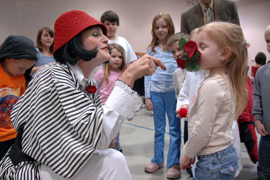 Pearl, a mime from the Cirque de Soleil's Saltimbanco touring troupe, lets Kaydence Erickson, 3, smell a rose after giving her a clown nose during their performance April 1 at the Offutt Youth Center. The performance featured stilt walkers and mimes. The Cirque du Soleil's touring troupe came to Offutt as part of a special 'Month of the Military Child' event during their regular promotional stops for their show in Omaha. (U.S. Air Force Photo/Josh Plueger)