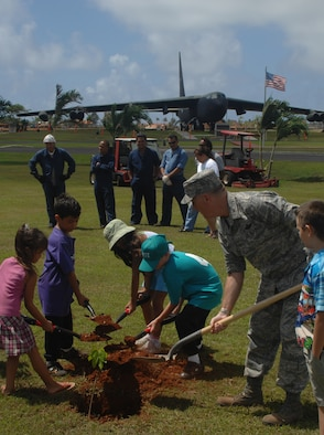 Col. Gregory Cain, 36th Wing vice commander, digs a hole to plant an Ifit tree with the help of several junior Team Andersen members during Andersen's Earth Day April 19 here. (U.S. photo by Airman 1st Class Zachary Hunter)