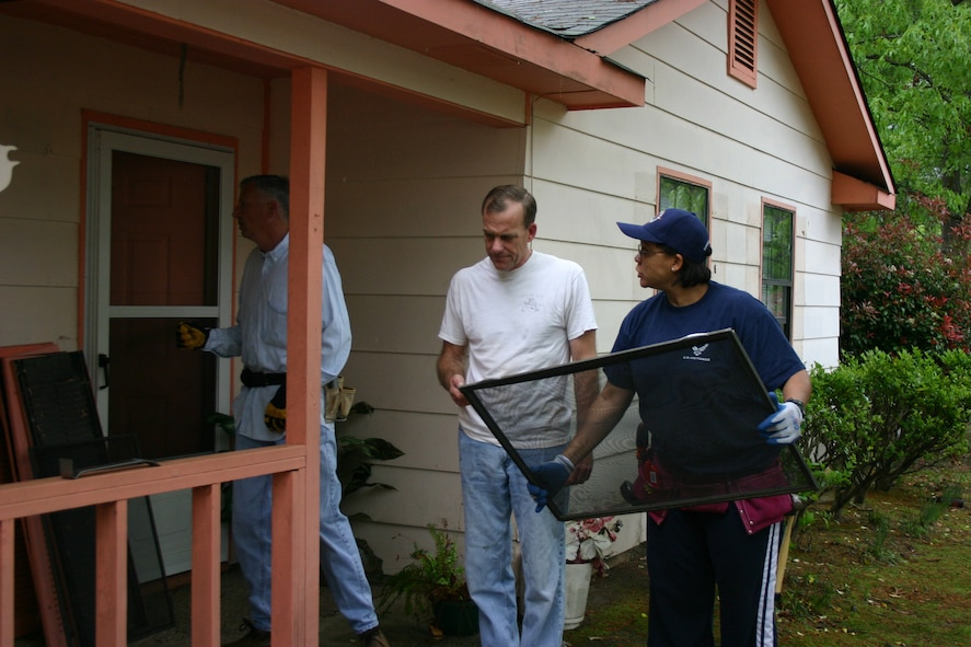 Chief Master Sgts. Dianne Bowe and Tom Kamps discuss replacing screens as Senior Master Sgt. Tim Foley reaches for another screen for a house they helped rehab April 19 in Warner Robins, Ga., through a volunteer program called Rebuilding Together. They are assigned to Headquarters Air Force Reserve Command, Robins Air Force Base, Ga., and worked with other volunteers in April to install new windows and screens, put in a new kitchen floor, and paint the outside of the house. (U.S. Air Force photo/1st Lt. Lisa Kostellic)