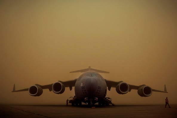 1st Lt. Matheew Lundeen (left) and Maj. Mark Thompson walk around their C-17 Globemaster III April 17 while it's parked on the flight line during a dust storm at Sather Air Base, Iraq. The dust storm reduced visibility to 100 meters and stopped all air traffic. (U.S. Air Force photo/Tech. Sgt. Jeffrey Allen)