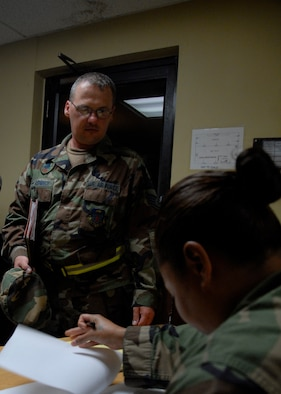 Airman 1st Class Shelley Walton, 36th Mission Support Squadron, verifies that Staff Sgt. Anthony Ashbeck, 36th Civil Engineer Squadron, is on a passenger manifest during the wing's Initial Response Readiness Exercise April 28. Before proceeding to the processing line for a pre-deployment briefing, each individual on the manifest must be accounted for. (U.S. Air Force photo/Staff Sgt. Patrick Mitchell)