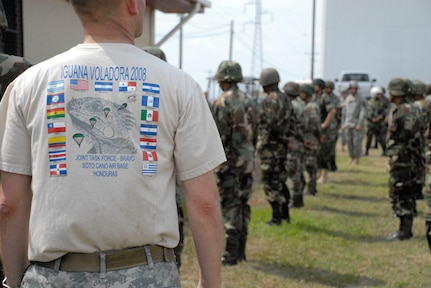 SOTO CANO AIR BASE, Honduras--Wearing a special event t-shirt, Army Lt. Col. Gregory Jicha, Iguana Voladora airborne commander, oversees the pre-jump instruction and familiarization the day before the jump. More than 135 paratroopers from 17 nations participated in this year's Iguana Voladora. (Photo by Tech. Sgt. William Farrow)