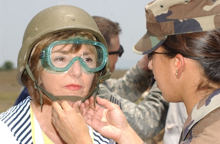 Air Force Capt. Kenya Colon, deputy director of logistics for Joint Task Force-Bravo, assists fitting a helmet on Joint Civilian Orientation Conference participant Nikki Clay. JCOC visited Soto Cano Air Base Apr. 24 as part of a tour of locations throughout the U.S. Southern Command area of responsibility. (Photo by Martin Chahin)