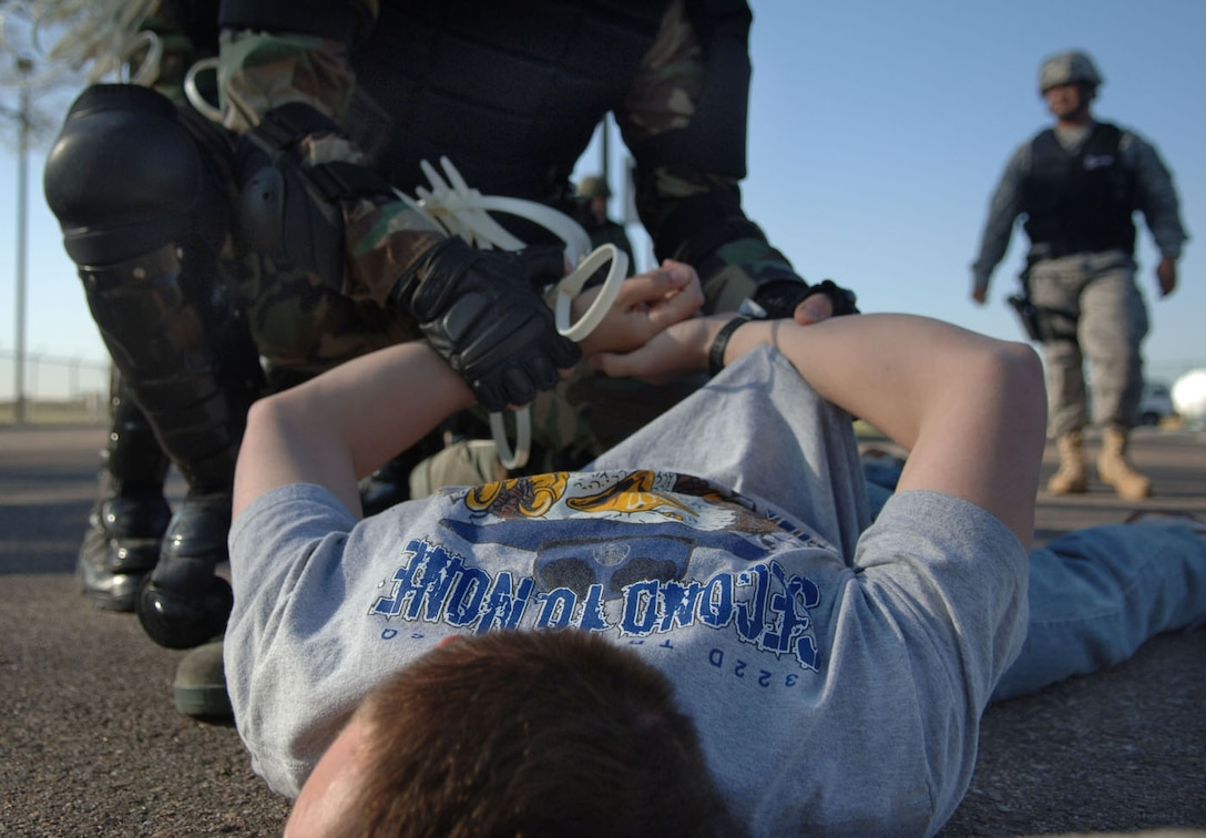 """BUCKLEY AIR FORCE BASE, Colo. -- A member of the 460th Security Forces Squadron detains a player during an """"exercise"""" protest held at the Sixth Avenue Gate here April 23. Buckley was inspected by the Air Force Space Command Inspector General team from April 20 - 28. (U.S. Air Force photo by Airman 1st Class Christopher Bush)"""