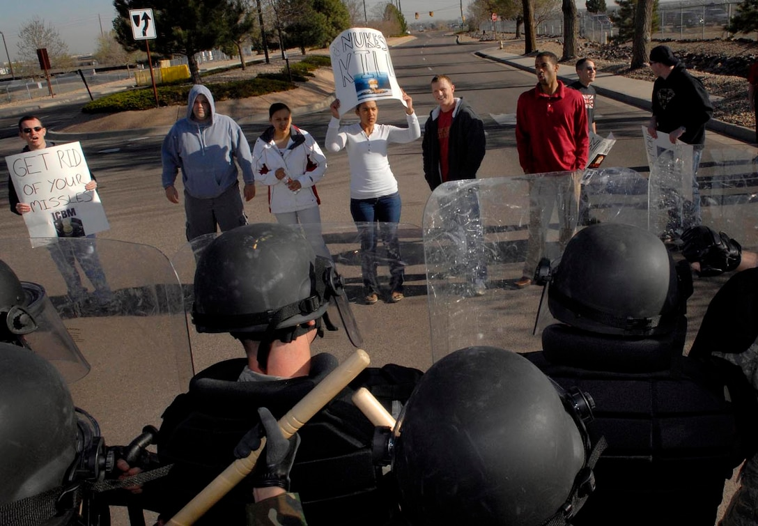 BUCKLEY AIR FORCE BASE, Colo. -- Airmen pose as protesters while the confrontaion management team guards the base during the base's Operational Readiness Inspection here April 23.(U.S. Air Force photo by Senior Airman Steve Czyz)