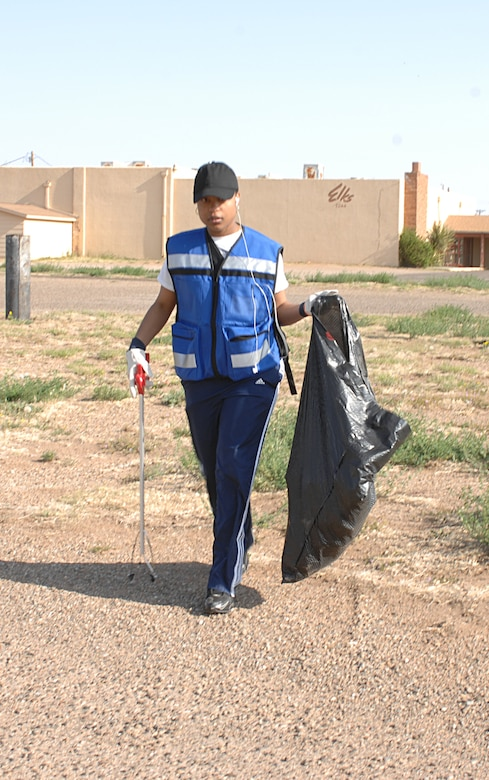 CANNON AIR FORCE BASE, N.M. -- Airman Shelly-Ann Douglas, 27th Special Operations Wing Security Forces Squadron, looks for more trash during the Great American Cleanup on April 26. Airman Douglas was one of more than 250 Airmen who particpated in the cleanup with Clovis, N.M., community residents and helped collect more than 94,000 pounds of trash, (U.S. Air Force photo by Greg Allen