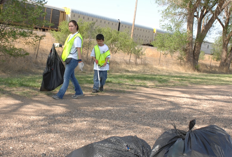 CANNON AIR FORCE BASE, N.M. -- Senior Airman Oralia Buenrostro, 27th Special Operations Medical Support Squadron, and her son, Juan, 9, pick up trash near the railroad tracks on Mabry Drive in Clovis, N.M. More than 250 Airmen participated in the Great American Cleanup effort on April 26, and with the community, collected more than 94,000 pounds of trash. (U.S. Air Force by Greg Allen)