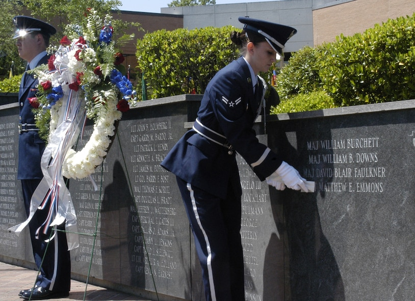 Honor Guardsman Amanda Fitzgerald removes the tape covering 2nd Lt. Matthew Emmons's name on the memorial wall in Smith Plaza Tuesday at the memorial service. Both Lieutenant Emmons and Maj. Blair Faulkner's names were engraved in the wall. (U.S. Air Force photo by Airman Josh Harbin)