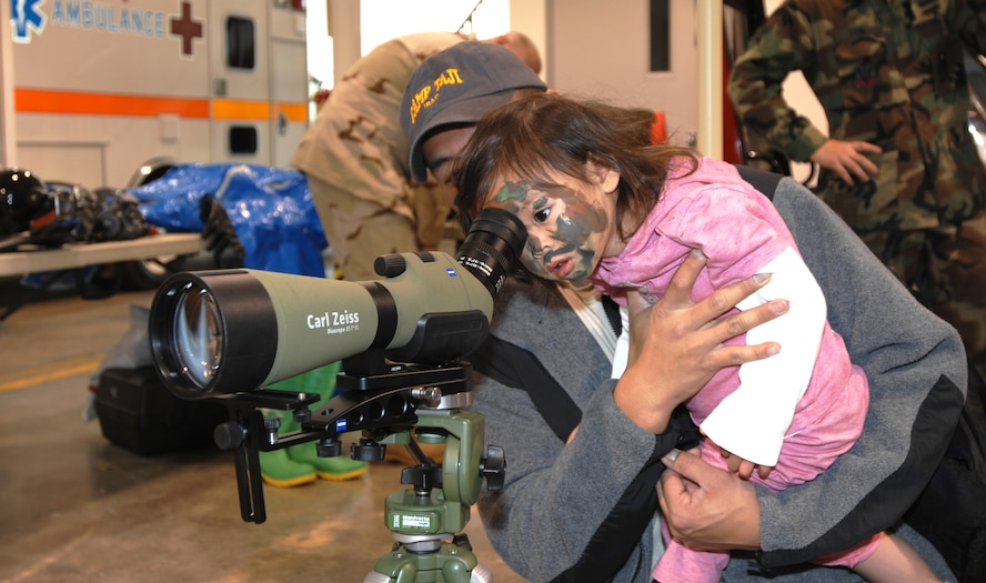 WHITEMAN AIR FORCE BASE - Tristen Vicuna looks through a scope while her dad holds her up to see through the scope during Operation Spirit April 26. Several squadrons came together to allow children to receive some hands-on experience with some of the equipment used during a deployment. (U.S. Air Force photo/Staff Sgt. Jason Barebo)