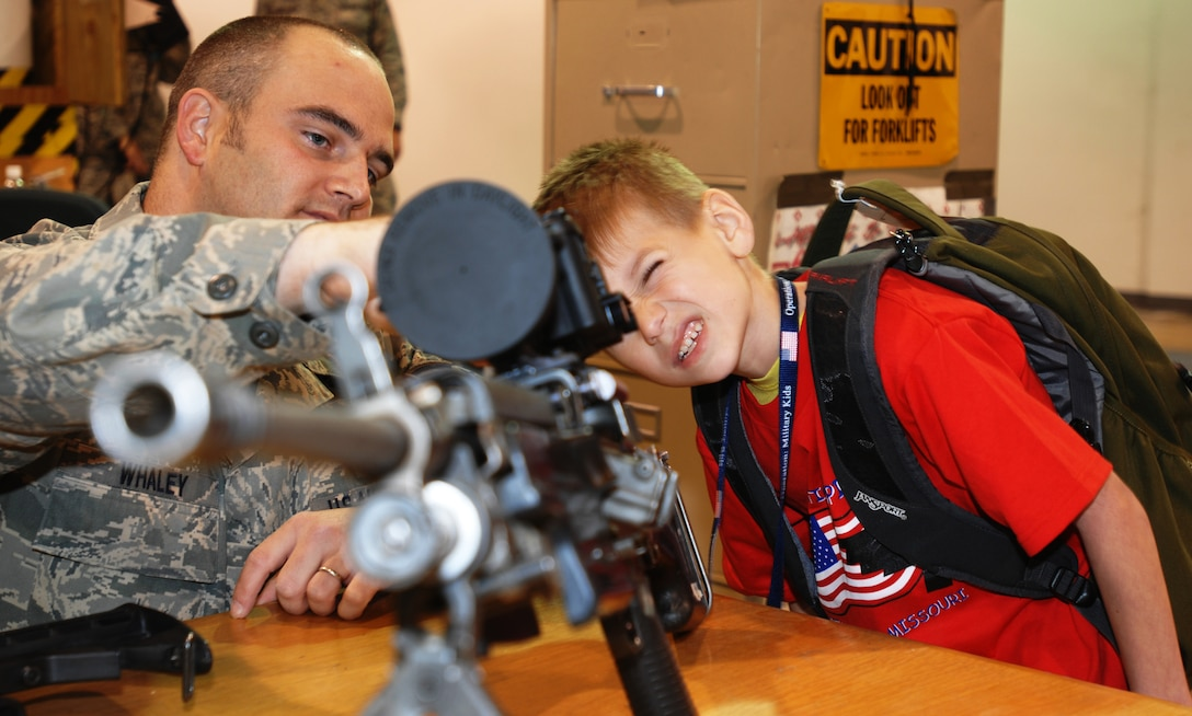 WHITEMAN AIR FORCE BASE - Staff Sgt. Charles Whaley (left), 509th Security Forces Squadron, makes adjustments for Justin Laurie (right) as he looks through a scope attached to a M249 during Operation Spirit April 26. the 509th SFS was available throughout the event to answer questions and give the children some hands-on experience with some of the equipment they use. (U.S. Air Force photo/Staff Sgt. Jason Barebo)