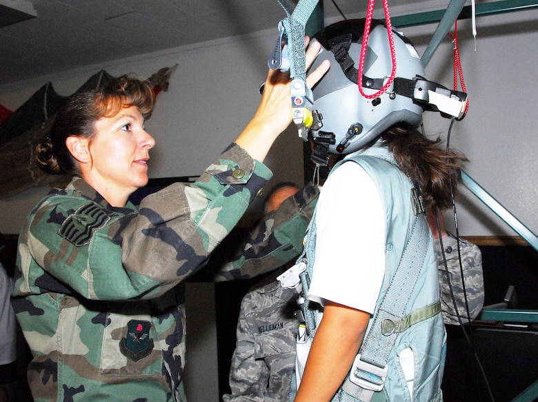 Tech. Sgt. Victoria Lacey shows a fourth-grade student the parachute simulator at the 162nd Operations Group. The tour, organized for the Wright Flight program, showed local school kids several examples of jobs found in the Air National Guard. (Air National Guard photo by Master Sgt. Dave Neve)