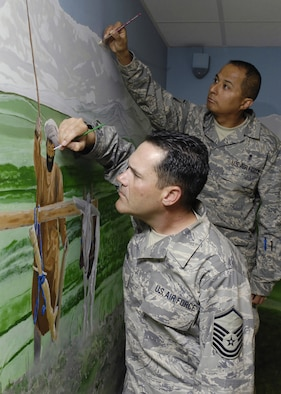 BAGRAM AIR FIELD, Afghanistan - Master Sgt. Albert Greig (front), Craig Joint Theater Hospital medical logistics superintendent, and Master Sgt. Cruz Torres Jr., NCO-in-charge Emergency Room, perform some final touch ups on a mural they and other artists painted in the hospital conference room here April 24. The mural features local culture and a panoramic view of the mountains from Bagram. Sergeant Greig is deployed from the 1st Special Operations Support Squadron, Hurlburt Field, Fla., and Sergeant Torres is deployed from the 710th Medical Squadron, Offut Air Force Base, Neb. (U.S. Air Force photo by Master Sgt. Demetrius Lester)
