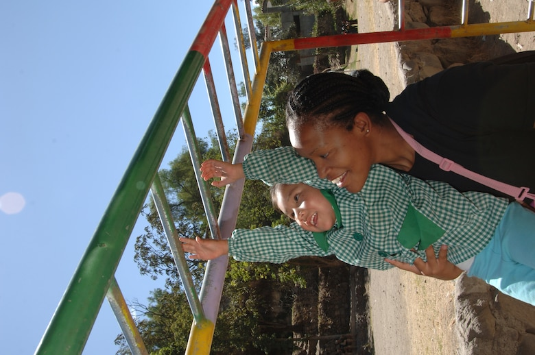 Airman 1st Class Laruen Russell, Task Force New Horizons information manager, helps a Peruvian child swing across the monkey bars at the local Ayacucho zoo's playground, July 25.  Task force members treated children at the school on post to a day at the museum and school as part of New Horizons community outreach. (U.S. Air Force photo by Capt. David Tomiyama)