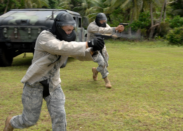 Staff Sgt. Daniel Gonzalez from Kadena Air Base, Japan and Staff Sgt. Robert Bishop from Misawa Air Base, Japan participate in  a live fire scenario during the Commando Warrior Simuntions training exercise July 30 at Andersen Air Force Base, Guam. M-9 and M-4 Simunition configured training weapons and colored FX rounds were used during the training course. Security Forces airmen from across  the Pacific Air Forces came together to perform the training hosted by the 736th SFS. (U.S. Air Force photo by Airman 1st Class Nichelle Griffiths)