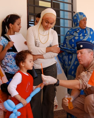 Lt. Col. Paul Byrd, humanitarian civil assistance commander with the 151st Expeditionary Medical Group, shows a young moroccan girl how to blow bubbles while she waits to be seen at a temporary clinic in July during African Lion 2008. (USAF photo by Master Sgt. Sterling Poulson)