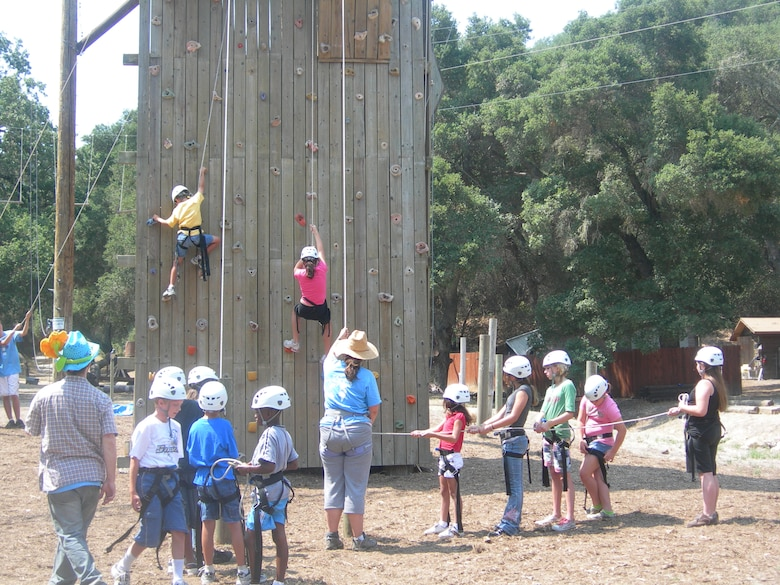 """CAMP WHITTIER, Calif. --  Children climb a """"rock wall"""" with the help of camp instructors at Operation Purple Camp here. OPC is a free, week-long camp open to children of military families. (Courtesy photo)"""
