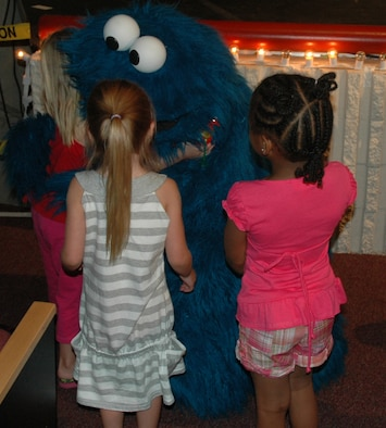 Cookie Monster takes the time to hug some children during a live performance at North Ridge High School in Layton, August 1.  (U.S. photo by Airman 1st Class Robby Hedrick)