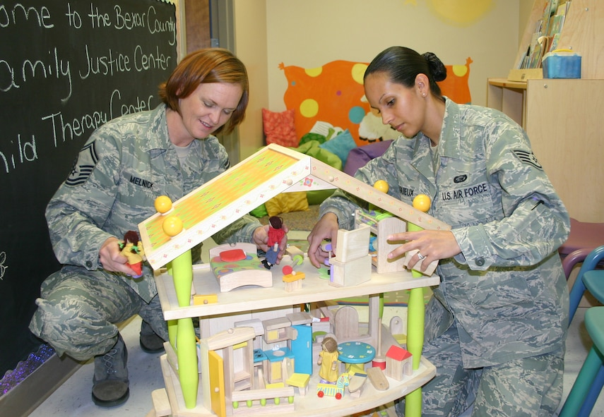 Senior Master Sgt. Carianne Melnick and Staff Sgt. Aidaliz Lagueux, both of the Air Force Personnel Center here, put the final touches on a dollhouse that will help children at a new child therapy center located in downtown San Antonio. (U.S. Air Force photo/Richard Salomon)