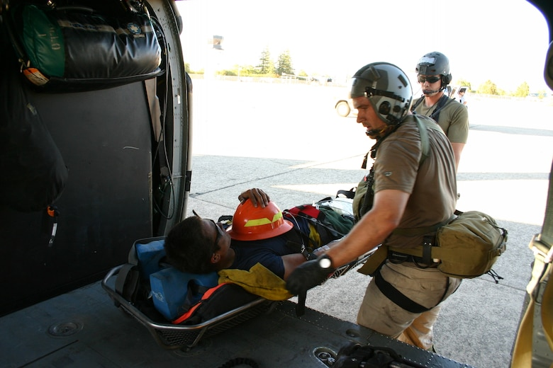 Tech. Sgt. Michael Bendle (left) and Staff Sgt. Seth Zweben (right), pararescuemen from the 131st Rescue Squadron, prepare to transfer a firefighter off of the 129th Rescue Wing-based HH-60G Pave Hawk to an awaiting ambulance at the Chico Municiple Airport, Calif., Aug. 4. The firefighter was working in the Feather River Complex near French Bear, Calif., when he suffered a heat stroke. The 129th Rescue Wing aircrew and pararescuemen hovered over steep terrain and hoisted the firefighter up in to the Pave Hawk. The total number of people saved by the 129th RQW is 561. (U.S. Air Force photo by Tech. Sgt. Brock Woodward)
