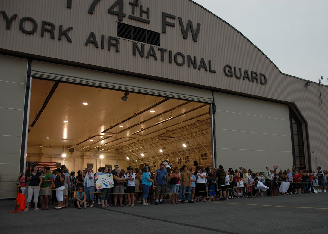 Family members of the 174th Fighter Wing gather in front of the hanger, awaiting the return of their loved ones.  The airmen and women of the 174th were deployed to South West Asia in support of Operation Iraqi Freedom.  The unit was deployed in early June for combat deployment.  This was the last scheduled F-16 deployment for the 174th Fighter Wing.  The wing will begin transitioning to the Reaper mission, an unmanned aerial vehicle, or UAV.