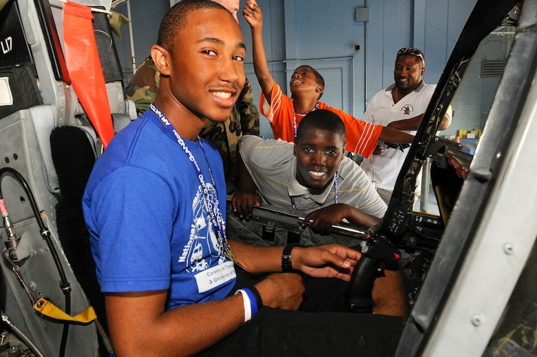 Diamante Astellero from the Summer Transportation Institute, Cheney University, Pa. sits in the pilot seat of an A-10 jet while Shane Walker and Edward Shepard, from Young Minds that Soar and Delaware Police Athletic League wait there turn to get into the plane. The 111th Fighter Wing hosted Tuskegee Airman Youth Day on Saturday July 19th.  Young men and women from Greater Philadelphia and Delaware came to ARS Willow Grove to meet Tuskegee Airmen and see up close aircraft such as an A-10, F-16, T-6A and P-3.