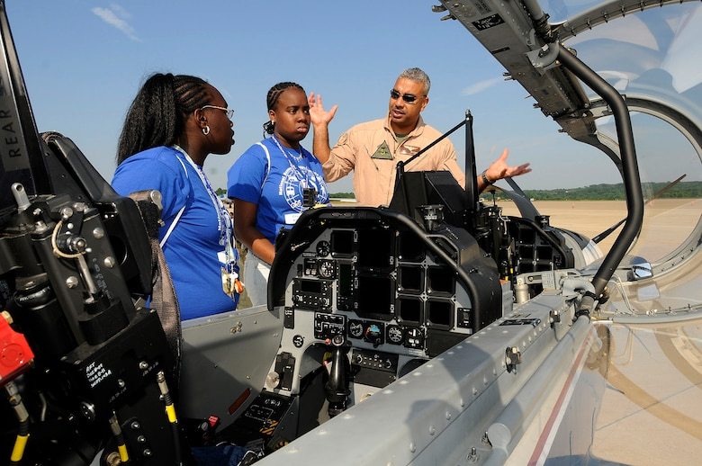 USMC Maj. Gregory Butcher from NAS Pensacola, FL T-6A explains the instruments inside of a T-6A to Regna Felder and her sister Janese Felder from the Summer Transportation Institute, Cheney University, Pa. The 111th Fighter Wing hosted Tuskegee Airman Youth Day on Saturday July 19th.  Young men and women from Greater Philadelphia and Delaware came to ARS Willow Grove to meet Tuskegee Airmen and see up close aircraft such as an A-10, F-16, T-6A and P-3.