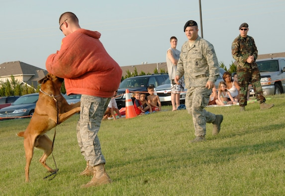 """MCCONNELL AIR FORCE BASE, Kan. –- Tech. Sgt. Andrew Bedell, 22nd Security Forces Squadron, is attacked by Military Working Dog Iindy while Iindy's handler, Staff Sgt. Matt Mosher, 22nd Security Forces Squadron, walks forward saying, """"Get'em"""", during a dog demonstration at National Night out at Rock River Rapids in Derby, Aug. 5. National Night Out is a way for citizens to participate in local anticrime programs with police and security forces. (Photo by Senior Airman Roy Lynch III)"""