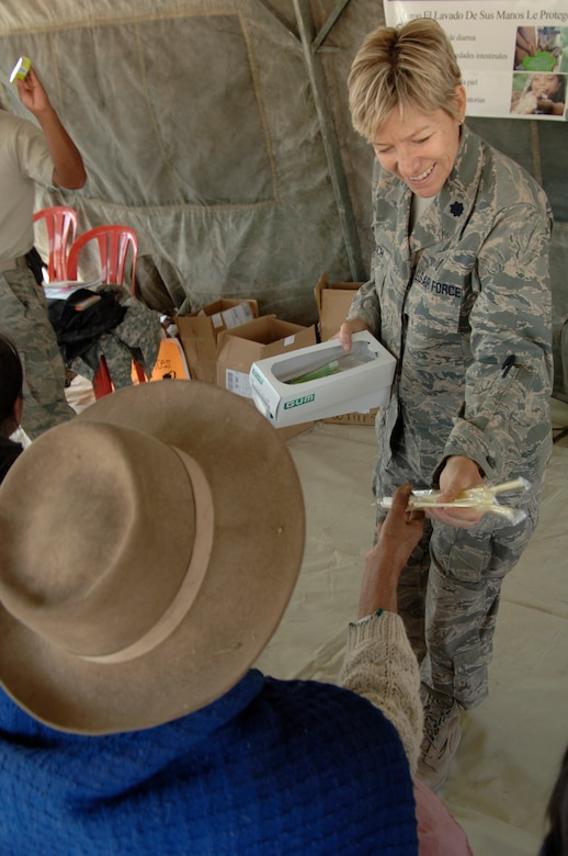 Lt. Col. Helen Crouch, from the 433rd Medical Group at Lackland AFB, Texas, passes out toothbrushes to Peruvian people listening to a public health lecture, Aug. 1, during a medical mission in Mollepata, Peru.  A team of 19 medical personnel deployed to Ayacucho, Peru to support the final three of nine medical missions supporting New Horizons - Peru 2008, a U.S. and Peruvian effort to bring humanitarian aid to underpriviliged Peruvians. (U.S. Air Force photo/1st Lt. Mary Pekas)