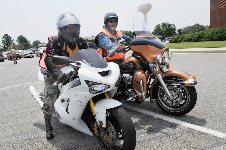 "Staff Sgt. Adria ""Dee"" Edwards, with her Kawasaki Ninja 636, and William Haffner, with his Harley Davidson Ultra Classic Electra Glide, show the proper equipment for motorcycle riding. That equipment includes helmet, gloves, boots, long sleeves and pants,and a reflective vest. If the rider is carrying a backpack it should be reflective as well.  U.S. Air Force file photo by Sue Sapp"