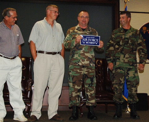 Master Sgt. Shelby Gobel holds up one of the gifts he received from fellow engineers during his retirement ceremony on Aug. 9.  Sergeant Gobel retired from the 931st Civil Engineer Squadron two years after he collided with a deer while riding a motorcycle.