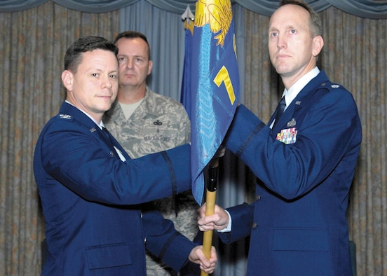 Colonel Wilkins F. Urquhart, commander, 3th Field Investigations Squadron, hands over the squadron guidon to Lt. Col. Adam C. Engleman, the new commander of the 7th Field Investigations Squadron during an assumption of command ceremony on Jul 28. Lt. Col. Engleman hails from Shaw AFB, S.C., where he was the director of the AFOSI Special Staff. (U.S. Air Force photo/Bobby Jones)
