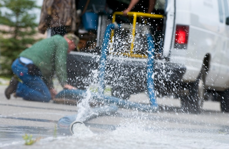 Denis Murphy a Davis, Gonzalez, and Rodriguez maintenance employee pumps water out of a flooded utilidor Aug. 7, 2008, at Eielson Air Force Base, Alaska. Eielson received more rainfall in the past couple weeks than it receives all year. With this much rain fall in a short amount of time the local area is experiencing mass flooding; there are currently more than 65 homes that have up to six inches of water in their basements. The DGR housing maintenance office is working on restoring all basements that have water damage. (U.S. Air Force photo by Airman 1st Class Jonathan Snyder) (Released)