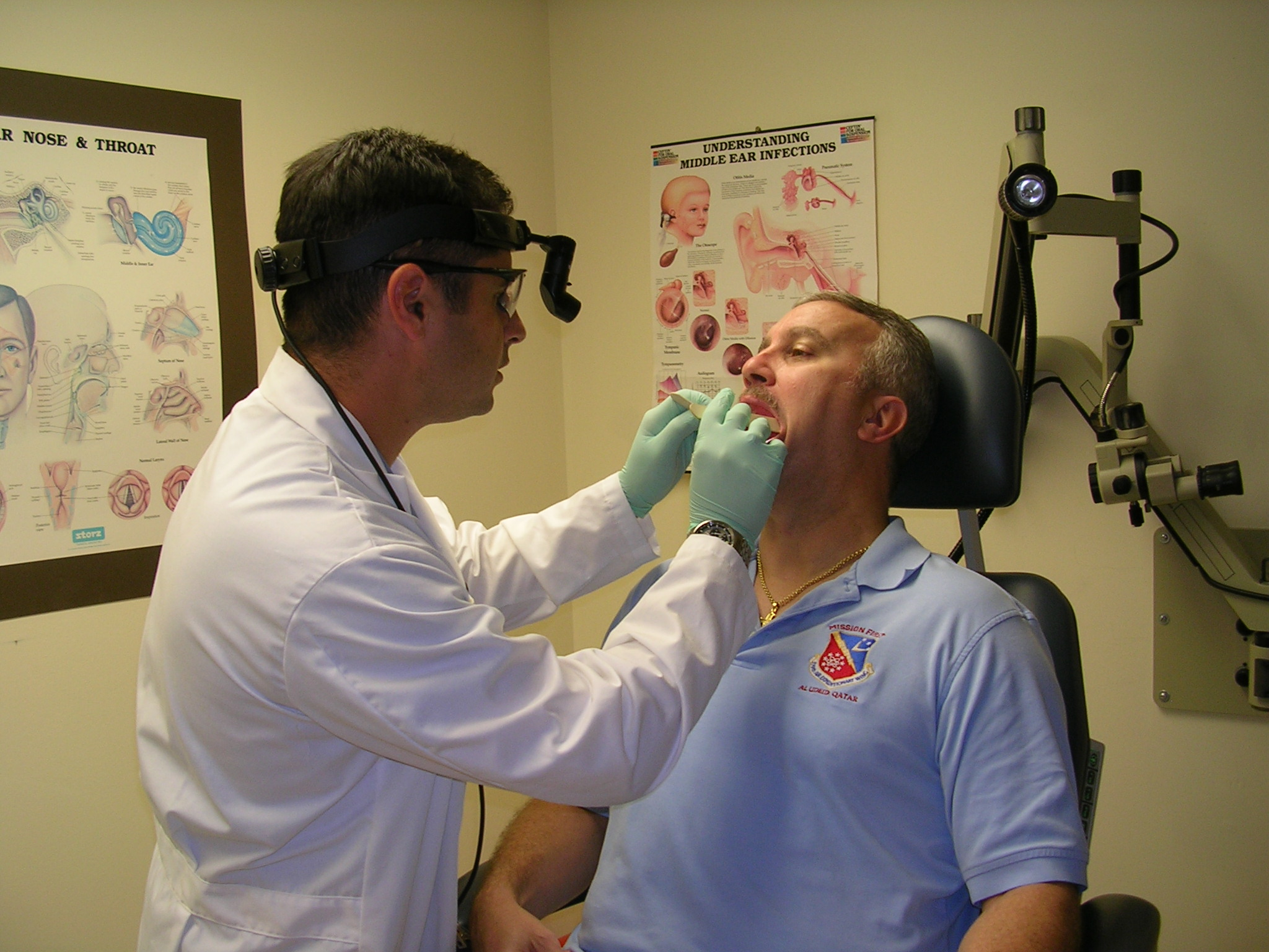 Doctor checking a man's mouth in an exam room.