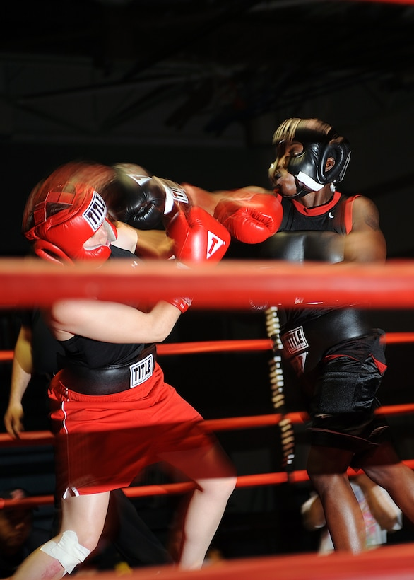 Tech. Sgt. Genese Williams, 49th Materiel Maintenance Support Squadron lands a punch on her opponent, Army 2nd Lt. Emma Taylor during their boxing match at Fort Bliss Army Post in El Paso, Texas,  July 25. The bout was an exhibition due to the differences in weight class. (U.S Air Force photo/ Airman 1st Class DeAndre Curtiss)