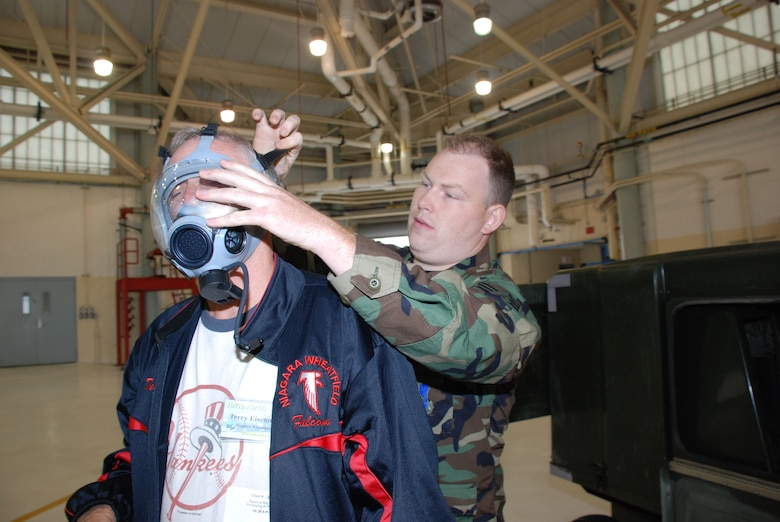 Senior Airman Shea, fits Terry Eisenman for a gas mask. Employers had the opportunity to see and try some of the equipment Airmen are issued and have to train with. (Air Force Photo/ Master Sgt. Paul Brundage)