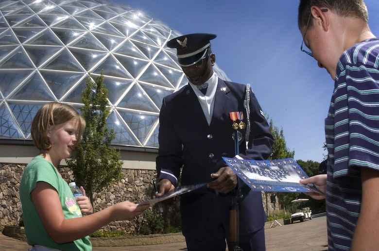 Marissa Colmar receives an autograph from one of Air Force Honor Guard drill team members Aug. 12 at the Henry Doorly Zoo in Omaha, Neb. Zoo visitors also had the chance to see the Do Something Amazing display featuring an F-16 Fighting Falcon, a motion simulator and video simulators during Air Force Week in the Heartland. (U.S. Air Force photo/Lance Cheung)