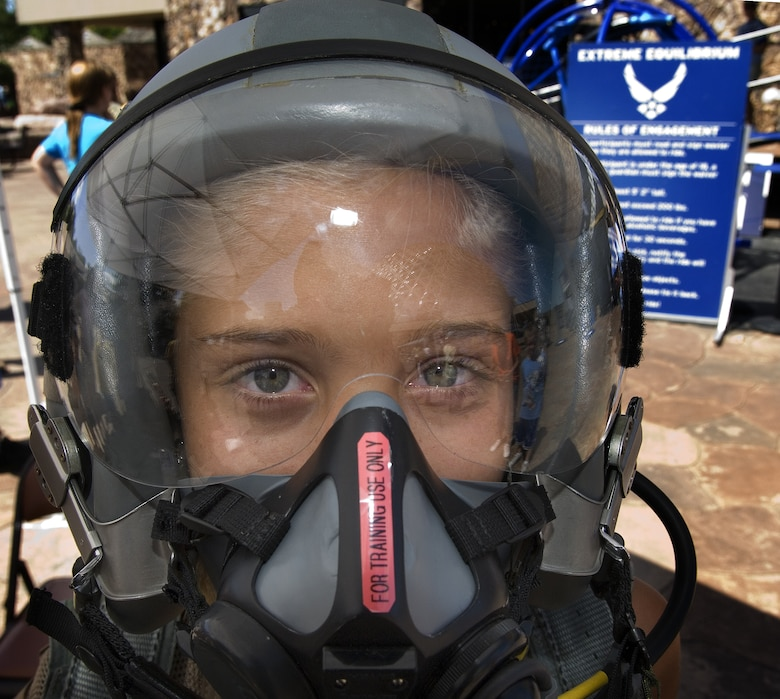 Kathryn Jacobs tries on fighter pilot gear during Air Force Week in the Heartland Aug. 12 at the Henry Doorly Zoo in Omaha, Neb. Zoo visitors also had the chance to see the Do Something Amazing display, a motion simulator and video simulators during Air Force Week in the Heartland. (U.S. Air Force photo/Lance Cheung)