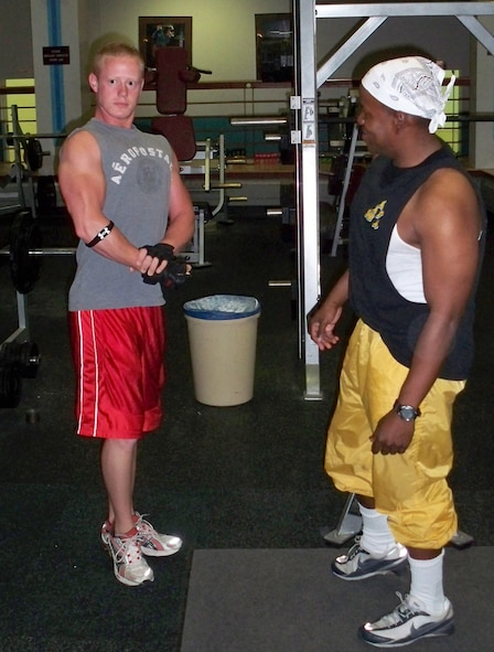 WHITEMAN AIR FORCE BASE, Mo. – Capt. Michael Boswell, 509th Logistics Readiness Squadron and WAFB bodybuilding coach, instructs Airman 1st Class Stephen Linch, 509th Bomb Wing Public Affairs, how to hold a pose that he will have to perform at the Sept. 27 North American National Bodybuilding Federation bodybuilding competition. Airman Linch is one of 12 WAFB Body Building Team members training for upcoming competitions.  (U.S. Air Force photo/Stephanie Fowler)