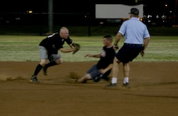 Talal Hafez, 3rd Radio Battalion utility player, slides past Christopher Oliger, Provost Marshall's Office Law Dawgs shortstop,  during the 2008 Intramural Softball League quarter final playoff game at Annex field Aug. 15.