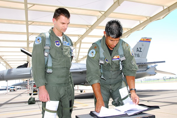 First Lt. Adam Jantas (left), a Polish Air Force student pilot, goes over his morning sortie with F-16 instructor pilot Maj. Julian Pacheco on the 162nd Fighter Wing flightline. (Air National Guard photo by Master Sgt. Dave Neve)