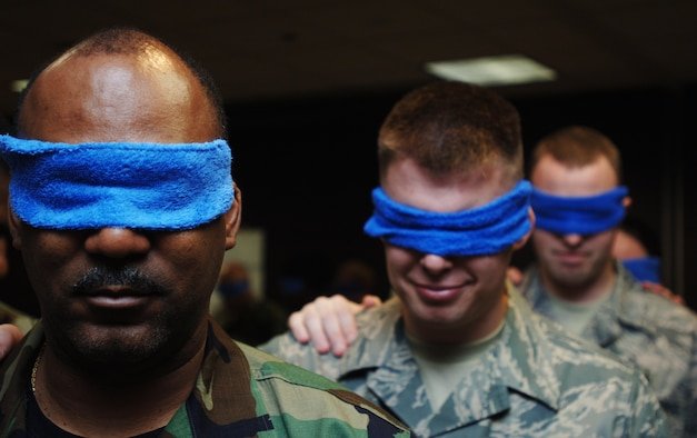 Tech. Sgt. Milton Willhight(far left), Senior Airman Nathen Hornecker (middle) and Staff Sgt. Keith Yoho wait to be led through a team-building exercise built into a two-week Noncommissioned Officer Leadership Development Program course that concluded on Aug. 15. The three Airmen were blindfolded to simulate vision loss from exposure to a poisonous gas. Sergeant Willhight and Airman Hornecker are assigned to the 931st Aircraft Maintenance Squadron. Sergeant Yoho is assigned to the 931st Aerospace Medicine Flight. (U.S. Air Force photo/Tech. Sgt. Jason Schaap)