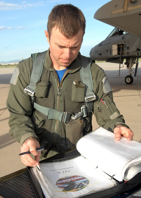 Captain Bryan Wojcik, 357th Fighter Squadron, checks the technical order ensuring everything is ready to go with the A-10C Thunderbolt II, here on Aug. 8, 2008.  Capt. Wojcik is a student with the squadron learning the new upgrade to the C-Model A-10. (US Air Force Photo By: Senior Airman Jacqueline Romero)