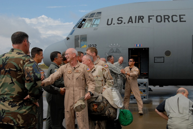 Col. Mark Kraus, commander of the 123rd Airlift Wing, is greeted as he deboards here.(Staff Sgt. Diane Stinnett/KyANG)
