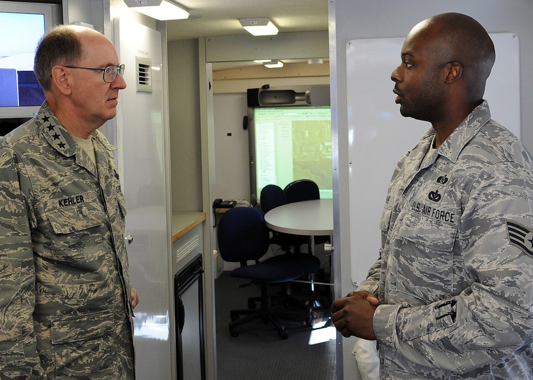 BUCKLEY AIR FORCE BASE, Colo. -- Staff Sgt. Othniel Evans, 460th Civil Engineer Squadron, informs Gen. C. Robert Kehler, Air Force Space Command commander, of the capabilities of the Mobile Emergency Operations Center during a tour of the vehicle. General Kehler spent Aug. 19 and 20 on the base visiting work centers for the first time since taking command of AFSPC in October 2007. (U.S. Air Force photo by Senior Airman Steven Czyz)