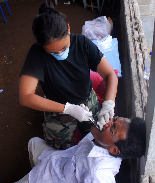 CLUBKI, Honduras - Dr. Alba Rivera, Honduran Army, takes out a man's tooth in a medical readiness exercise here Aug. 19. Dr. Rivera is part of a multi-national team training in an exercise to prepare for a disaster. Countries in the exercise include Honduras, Guatemala, El Salvador, and the United States. (U.S. Air Force photo by Staff Sgt. Joel Mease)